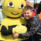 Photo of a boy hugging a bee mascot