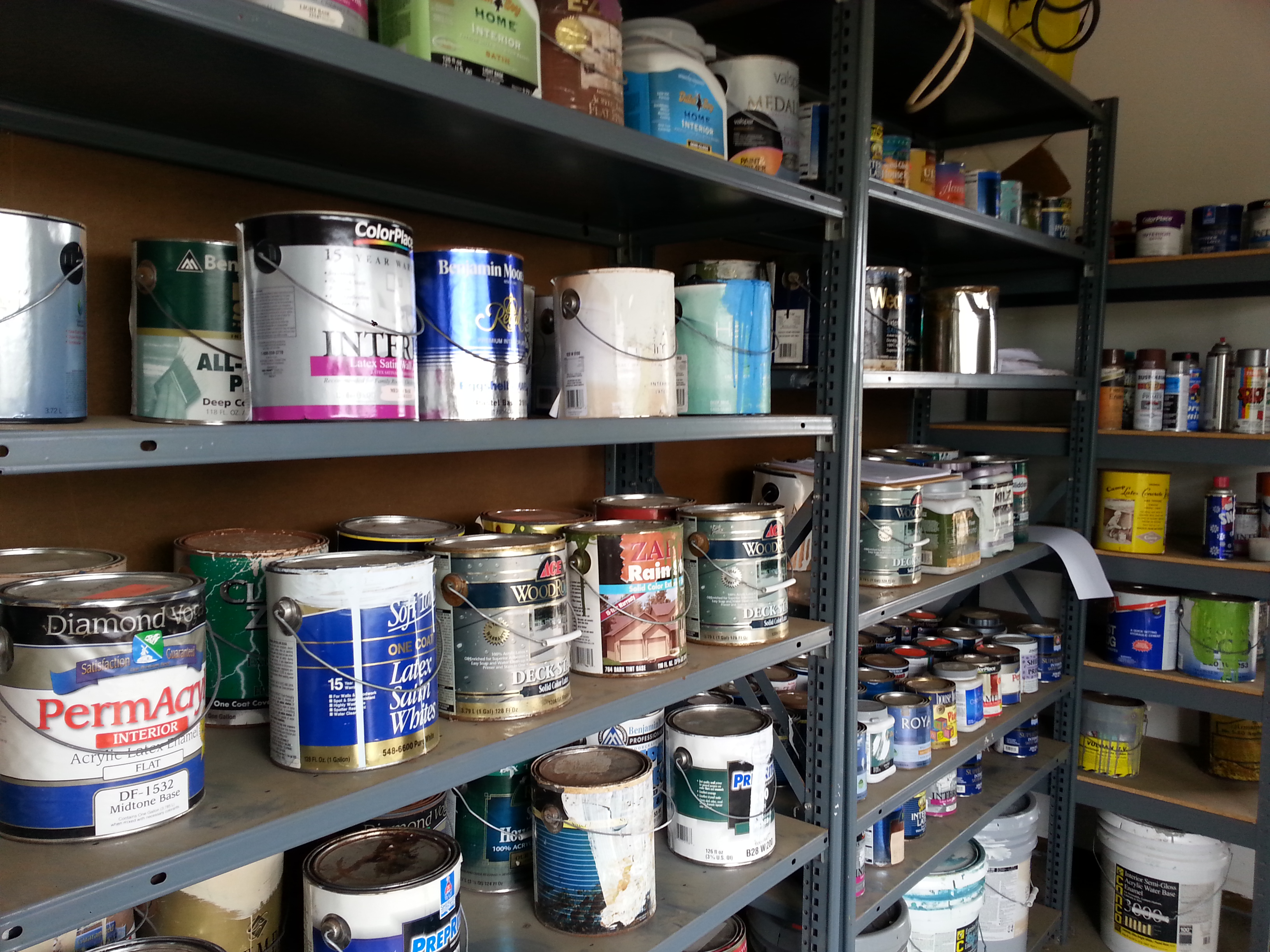 Photo of used paint cans on shelves