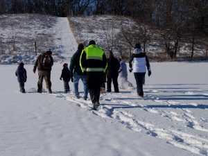 Photo of people walking through the snow