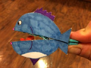 Photo of a fish eating fish on a clothespin